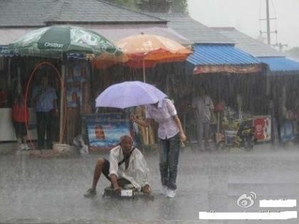 因腿部残疾而只能靠讨饭维生的大爷来不及避雨,只能望雨兴叹。突然,老人的头上多了一把雨伞。老人疑惑着抬起头,却看到了一位美丽的姑娘,雨伞已经完全偏向于老人,自己上衣、牛仔裤、运动鞋却完全湿透。而另一名制服男,却在棚下避雨,远远观望.jpg