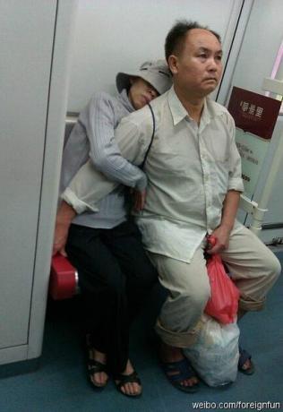 年度最爱情照片。没有拥抱,没有接吻,没有落日,没有沙滩,有的只不过是一个1米多的座位,男人体贴地伸出手挡住妻子的座位让她安稳睡觉,男人的眼中满是血丝,脚下是一包包的药,看得出男人很疲惫。如果一起甜蜜叫爱情,那么风雨同舟则是爱情的真谛。.jpg