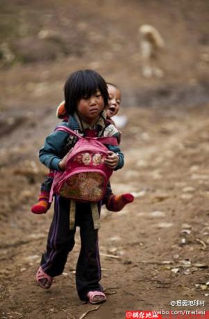 凉山州布拖县特里木镇日切村,寒冬降至,八岁的妞莫啦呷穿着凉鞋背着侄儿妞成王(音)走在去学校的乡间小路上。每当遇上颠簸的路面,小姑娘脚步蹒跚,孩子就在背后呵呵直乐。。。.jpg